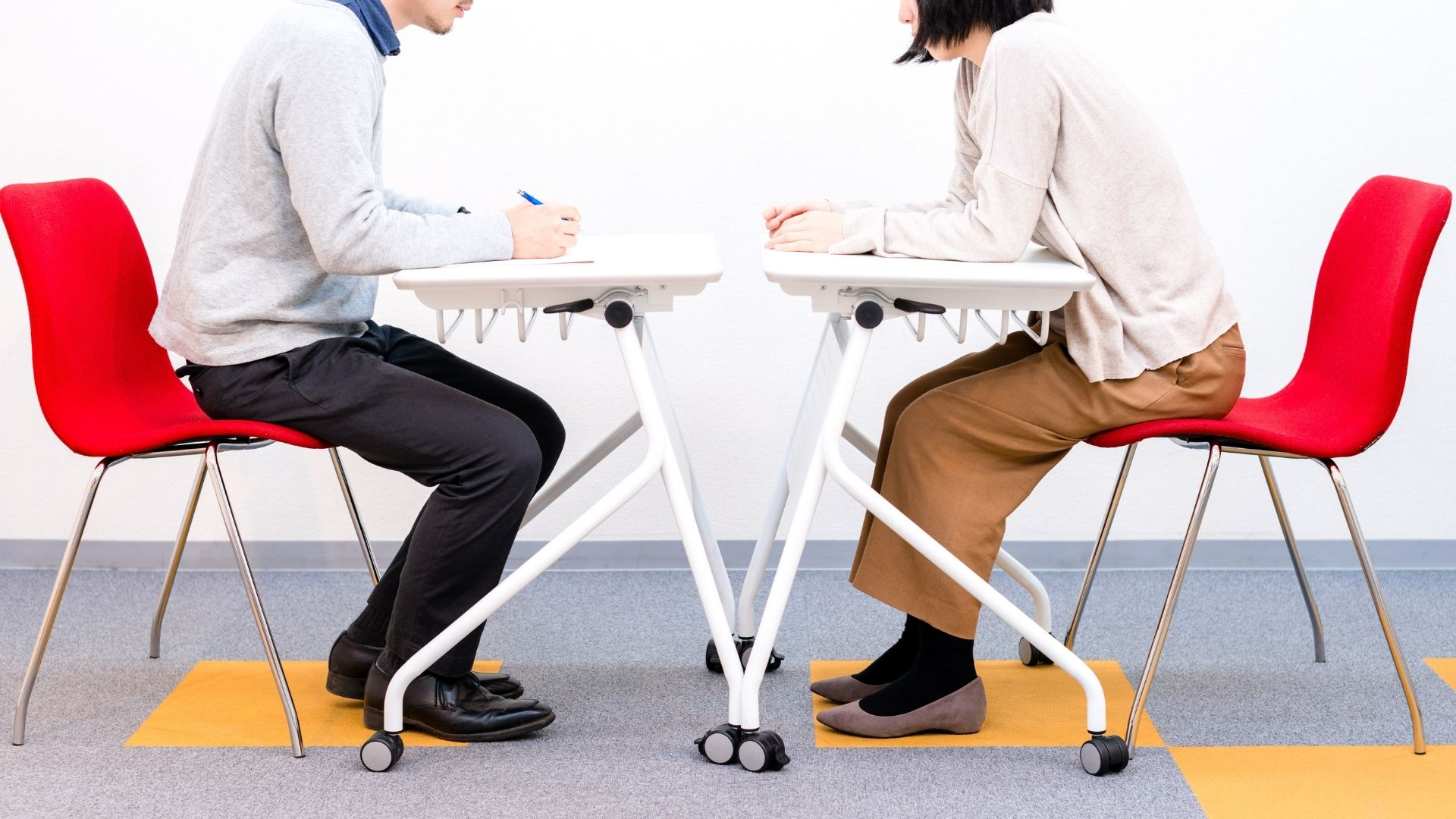 A young adult and a student sit across from each other in interview style stead in rolling chairs and desks — their faces are not visible