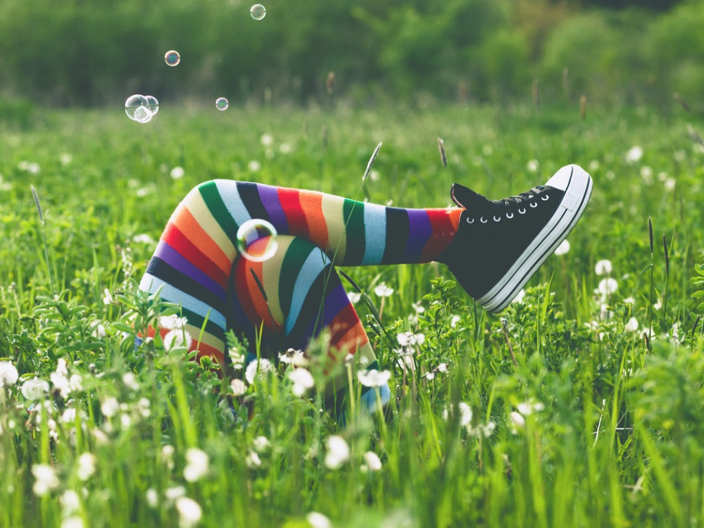 Teenager's legs in striped stockings showing amidst a field of flowers in summer.
