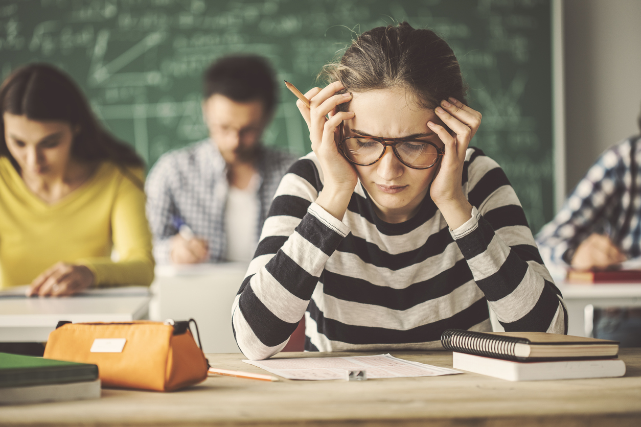 high school girl wearing striped shirt worrying over a test.