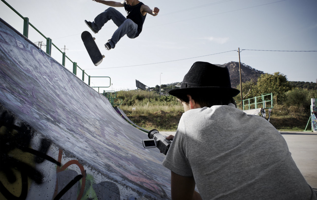 Teen filming skateboarder doing a kickflip on a halfpipe.