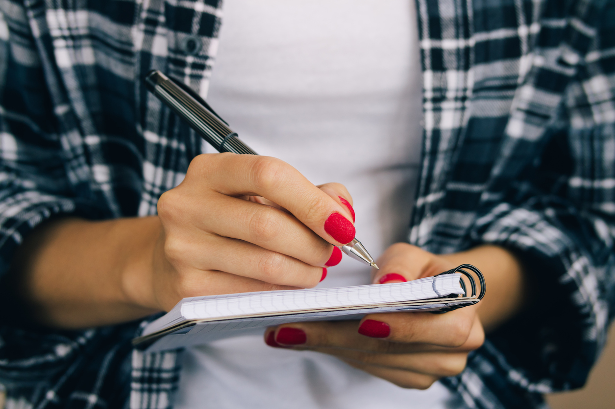 YOUng woman with red nails making a college list.