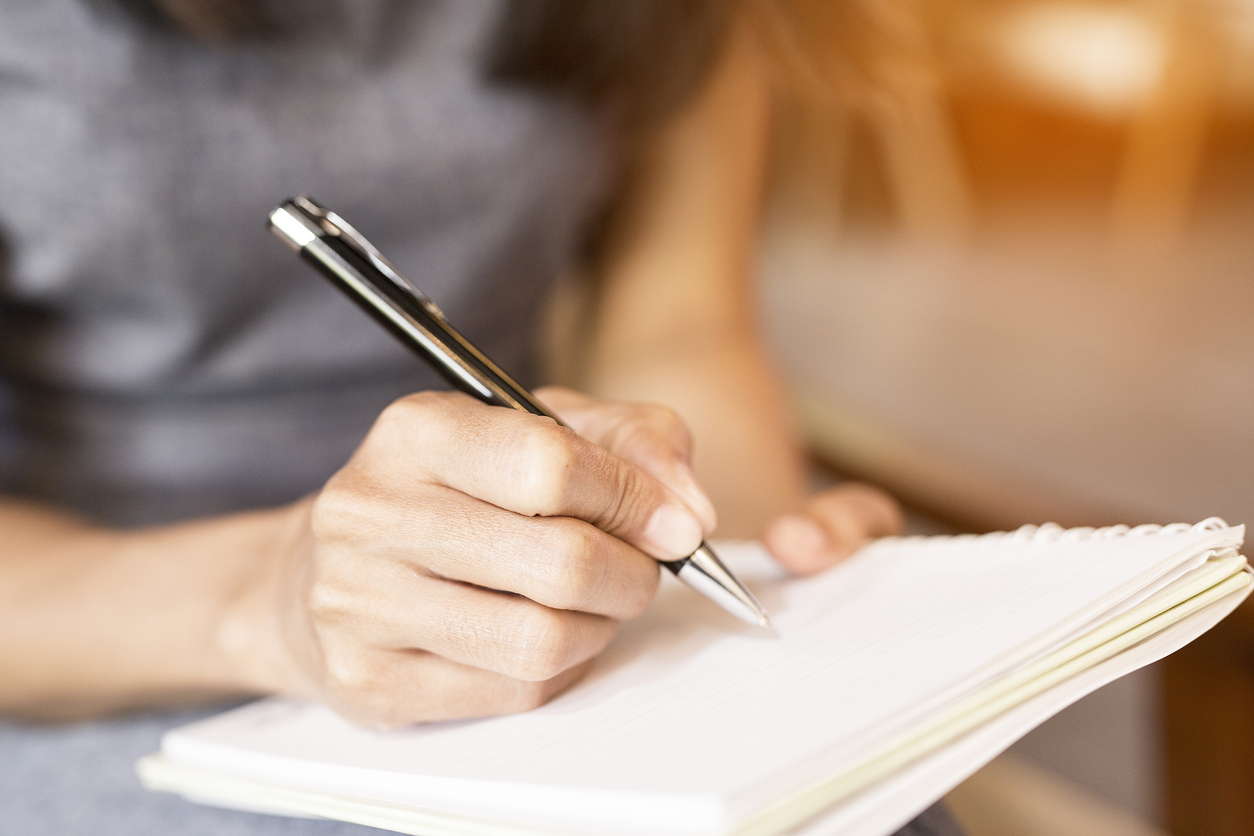 Woman's hand holding ballpoint pen and writing in notebook.