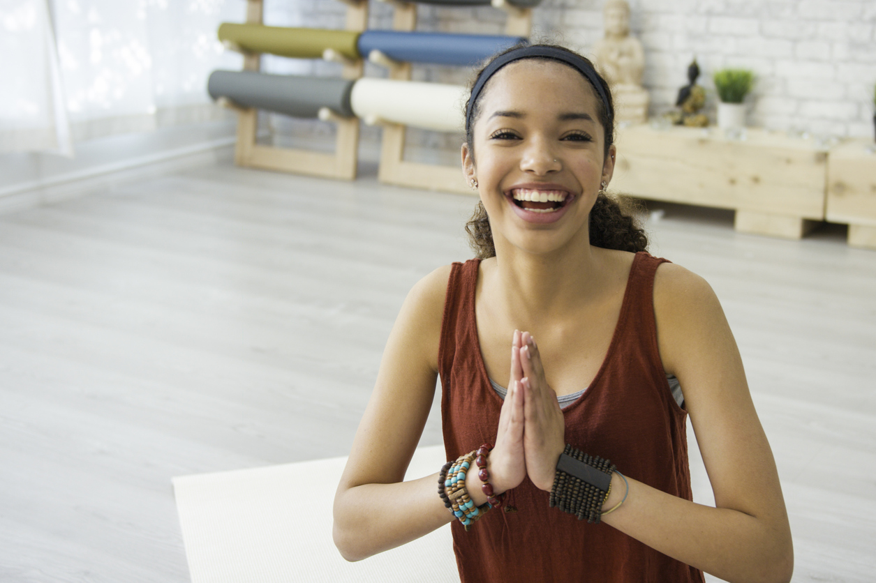 Teenage girl doing yoga and looking happy
