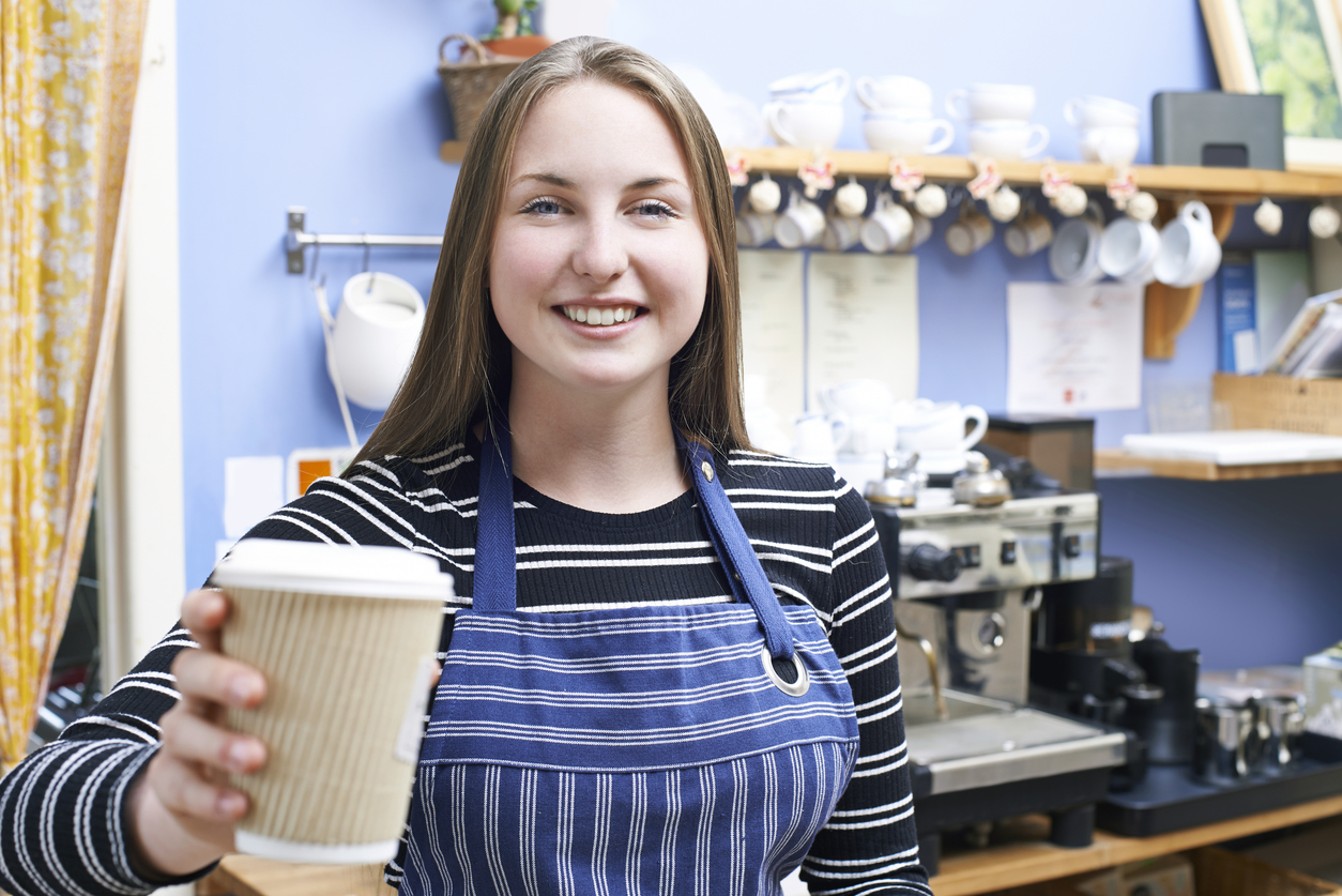 Teenage barista serving coffee at a cafe.
