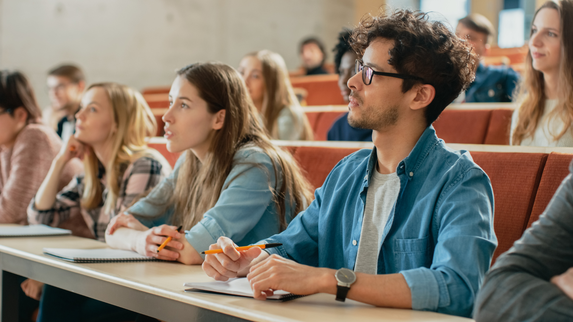 A Male and Female College Student Attend A Lecture With Other Students