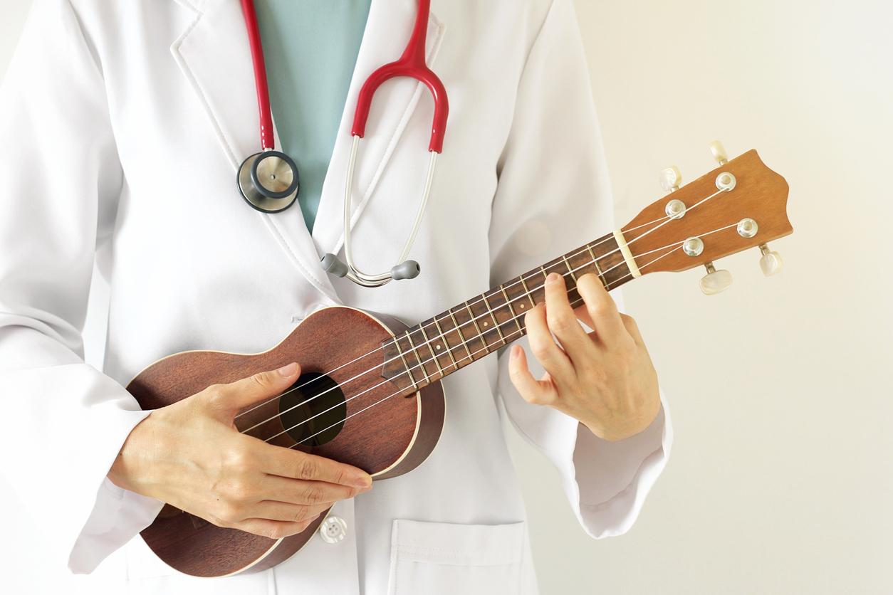 Doctor playing ukulele and wearing white coat.