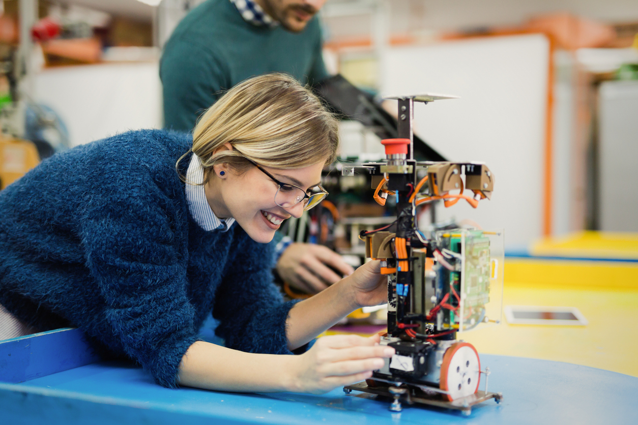 Young blond woman in blue sweater working on robotics.