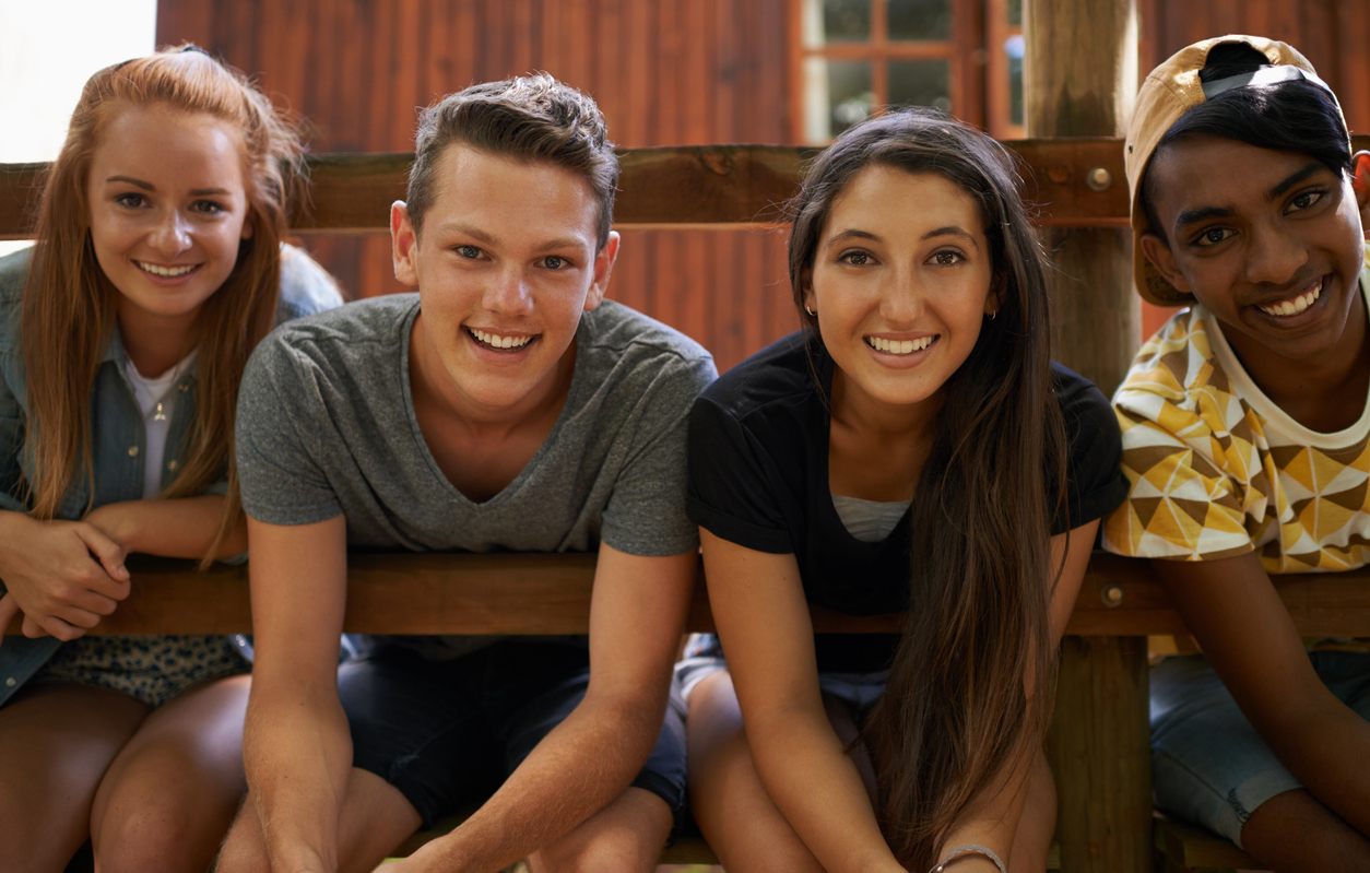Diverse group of four teenagers sitting on porch of summer camp cabin