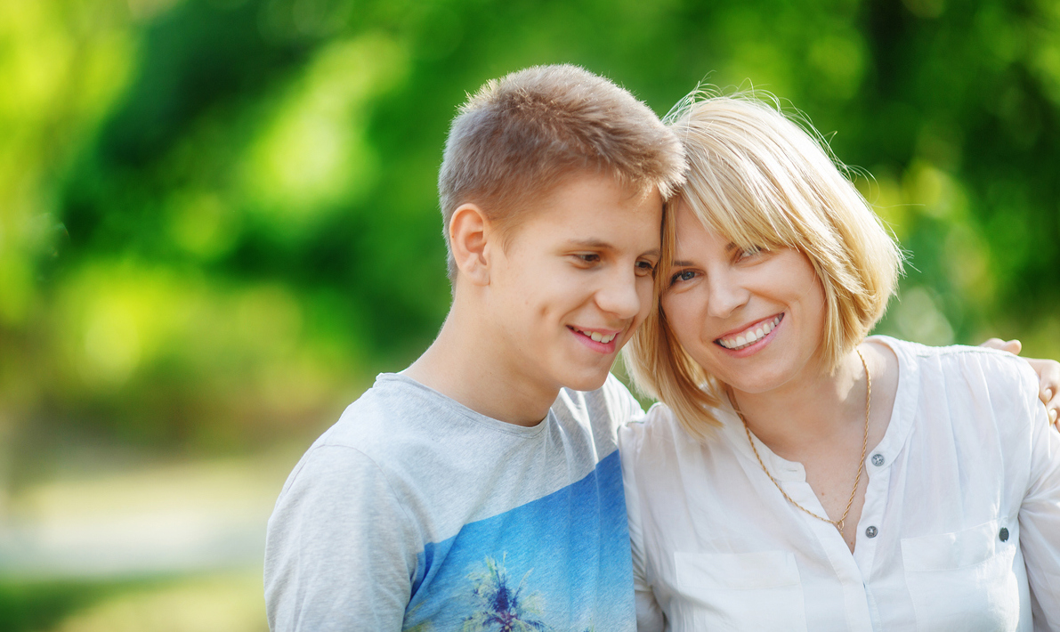 Mother and teen son bow their heads to each other for a walk in the park