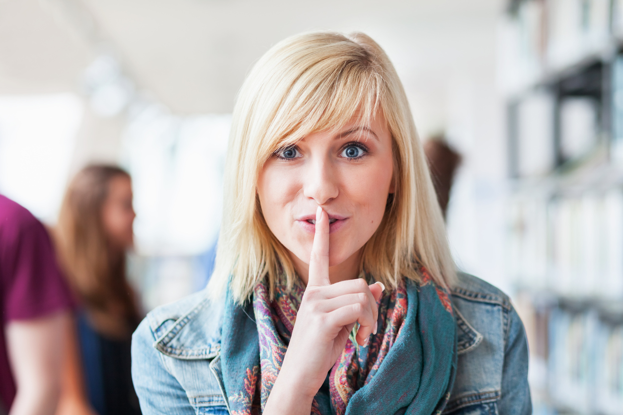 Woman shh-ing to keep one of the 5 secrets colleges don't want you to know.