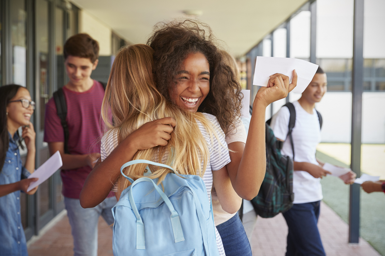 Two girls celebrating SAT results in school corridor